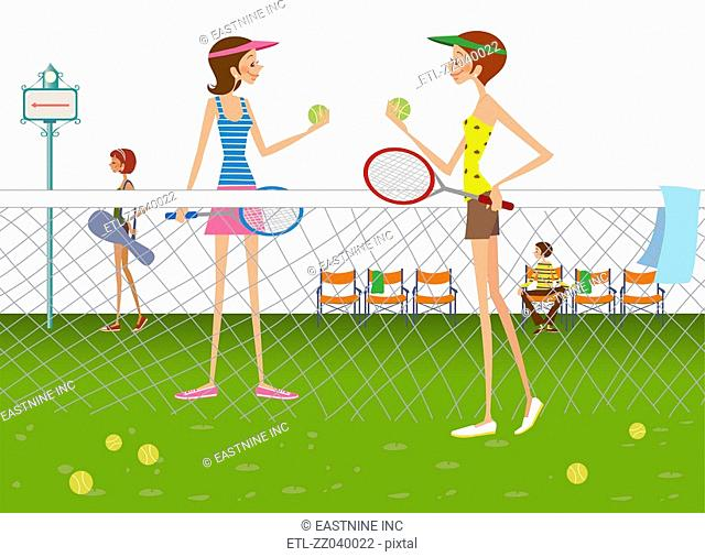 Two women standing in tennis court holding tennis balls and rackets