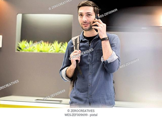 Man with back pack in office on cell phone