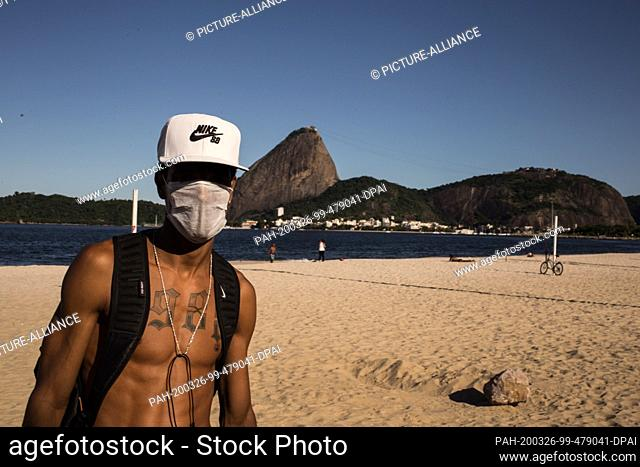 25 March 2020, Brazil, Rio de Janeiro: A man with a mask is going for a walk. In the background you can see the sugar loaf