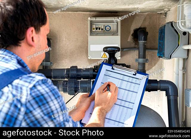Worker Holding Clipboard Inspecting Water Pump And Pipes