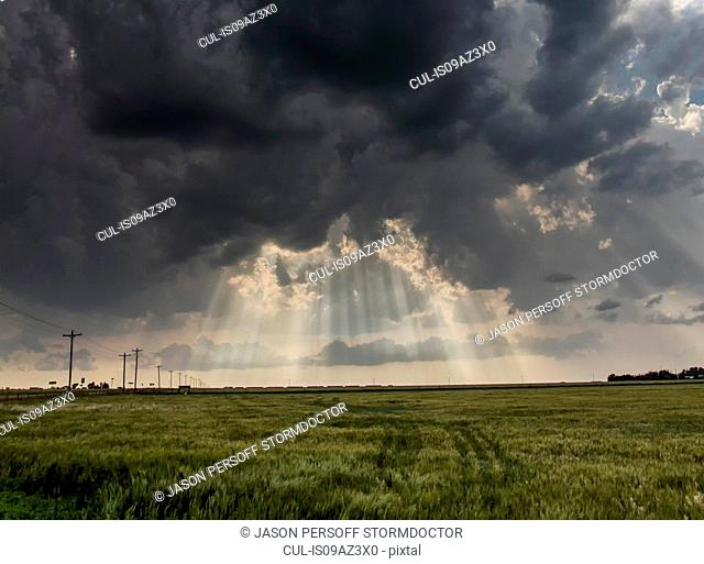 Crepuscular rays shining through clouds over country landscape following passage of a severe thunderstorm