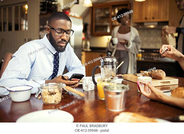 Businessman texting with smart phone at breakfast table