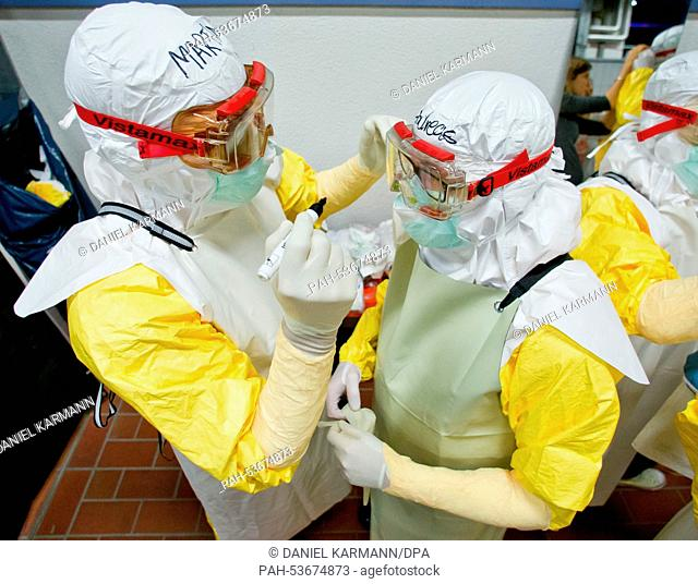Andreas (R) and Martin, participants of an Ebola training course, help each other put on their protective garments during preparations for work in crisis areas...