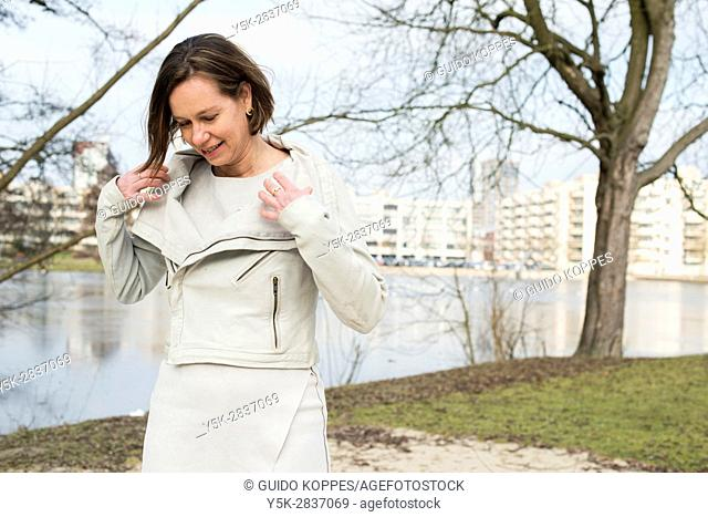 The Hague, Netherlands. Portrait of an adult caucasian woman in a park modelling her leather jacket
