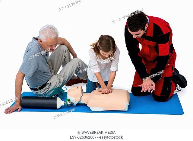 Paramedic training cardiopulmonary resuscitation to senior man and girl