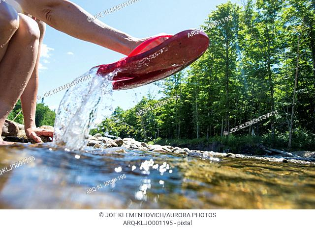 A Woman Removing Her Flip Flops From A Water On A Summer Day