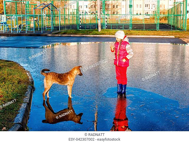 girl in white hat and red clothes standing in a pool playing with the dog on autumn sunny day
