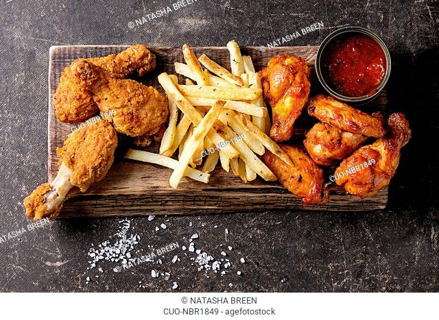 Fast food fried crispy and spicy chicken legs, wings and french fries potatoes with salt and ketchup sauce served on wooden serving board over dark texture...