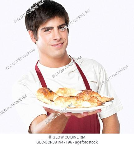 Portrait of a man holding croissants on a plate