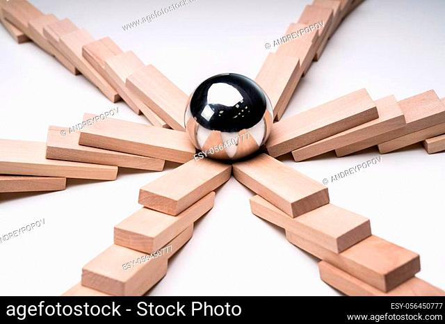 Close-up Of A Silver Ball In The Center Of Collapsed Wooden Dominoes Over White Backdrop