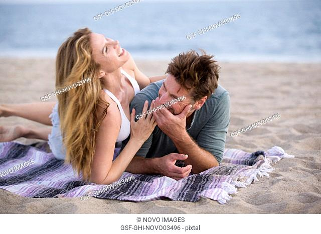 Laughing Mid-Adult Couple Laying on Blanket at Beach