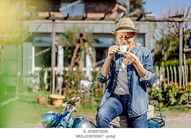 Woman on vintage motorcycle enjoying a coffee break