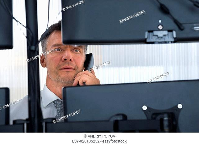 Mature male stock trader using telephone while looking at multiple computer screens at office
