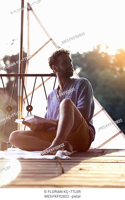 Young man with book sitting on a jetty next to sailing boat