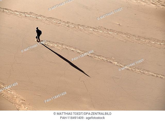 A tourist climbs the high surrounding dunes of the Deadvlei and throws a long shadow on the sand, taken on 01.03.2019. The Deadvlei is a dry