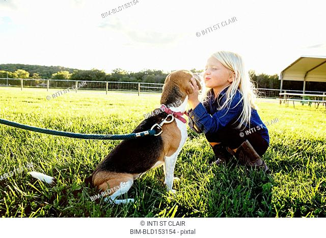 Caucasian girl kissing puppy on farm