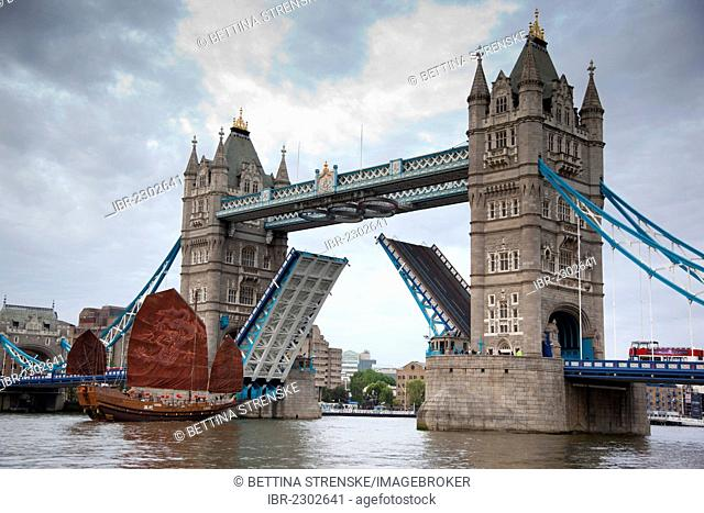 Chinese junk boat sailing through the open Tower Bridge on the River Thames, London, England, United Kingdom, Europe