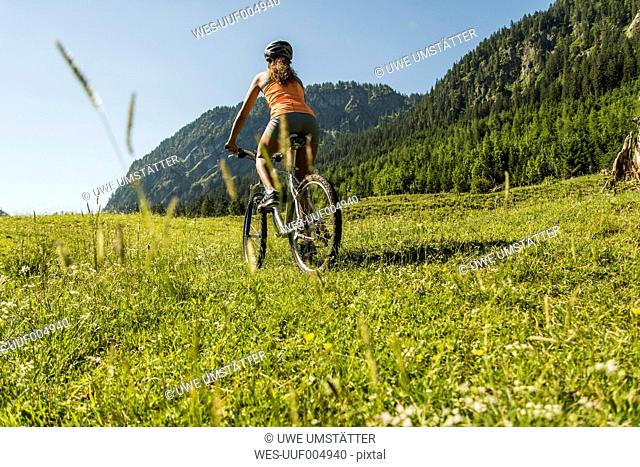 Austria, Tyrol, Tannheim Valley, young woman on mountain bike in alpine landscape