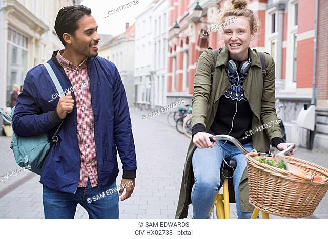 Young man and woman with bicycle on city street