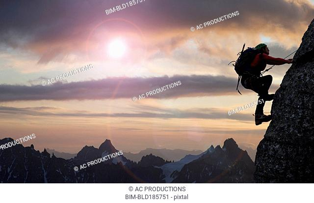 Caucasian climber scaling mountain in remote landscape