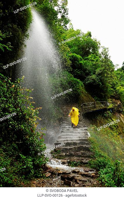 Hiker in rain coat cross small waterfall on the trail, Trek Langtang, Nepal