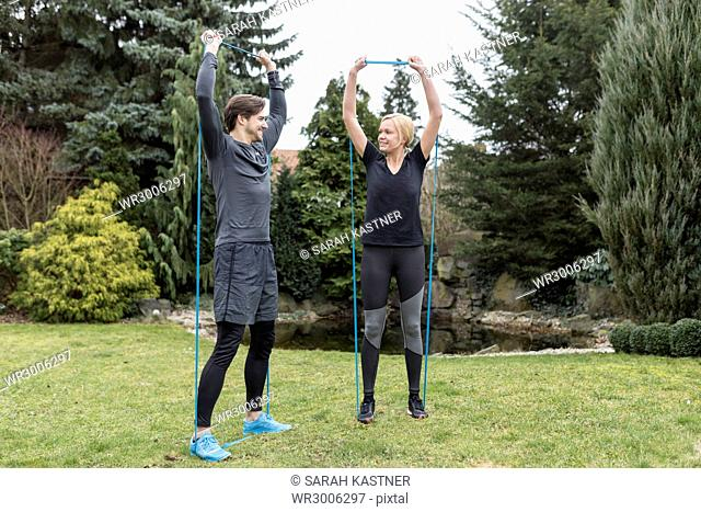 Couple is exercising together in the garden