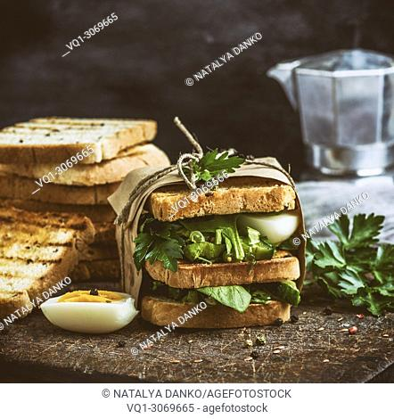 Sandwich of French toast and lettuce leaves and boiled egg, vintage toning