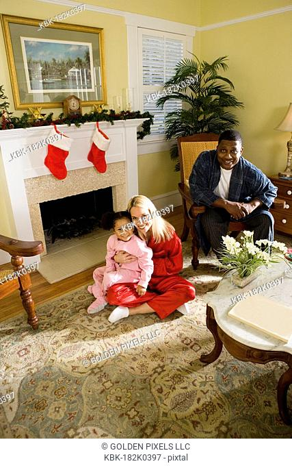 Family in pajamas sitting by fireplace decorated for Christmas