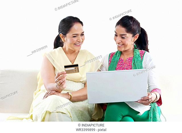 Mother and daughter with a laptop and credit card