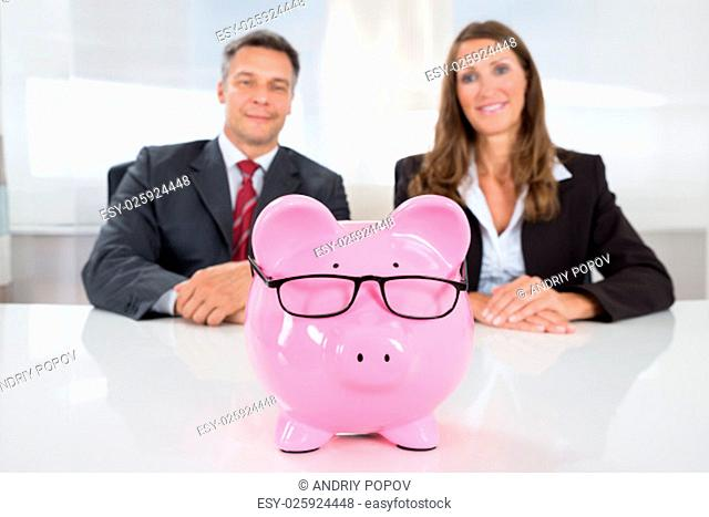 Two Happy Businesspeople Looking At Pink Piggybank On Desk