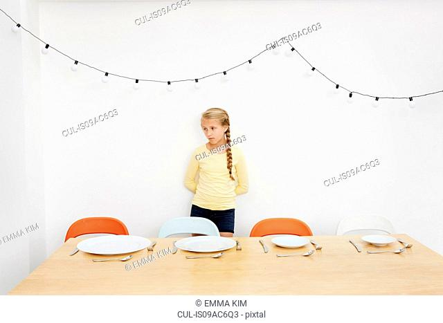 Girl waiting by table with empty plates