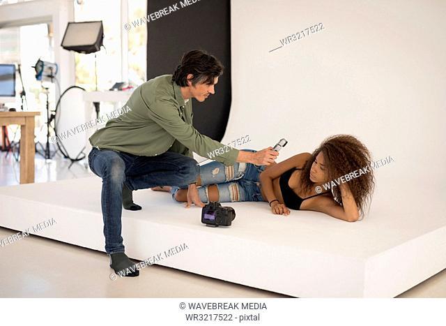 Photographer measuring light with light meter on female model