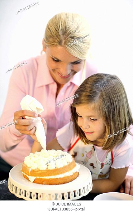Mother and daughter icing a cake together