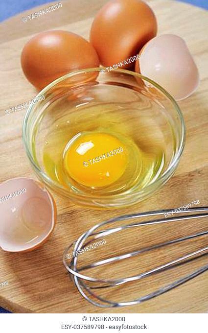 Raw chicken eggs on wooden cutting board