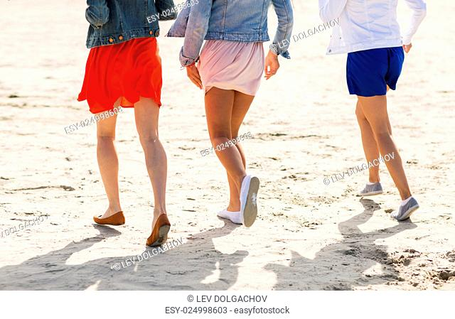 summer vacation, holidays, travel and people concept - close up of women legs running on beach