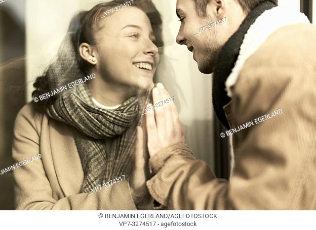 happy young teenage couple separated by window, trying to touch hands, in Cottbus, Brandenburg, Germany