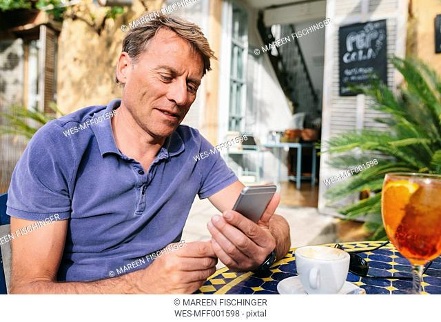 Spain, Mallorca, Arta, portrait of man sitting at courtyard of a cafe using smartphone
