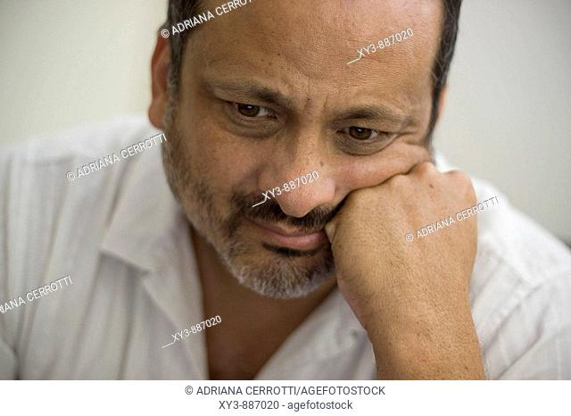 Middle age Latino man's losse up portrait with a gesture of concern