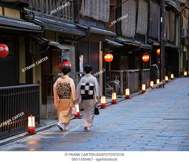 A Gion street lit up with paper lanterns showing two women in kimono walking down it