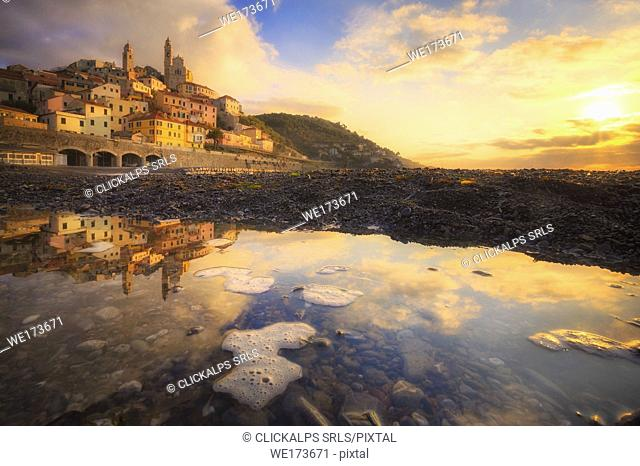 The village is reflected in a puddle on the beach during the sunrise. Cervo, Imperia province, Liguria, Italy, Europe