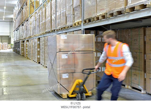 Man in factory hall using pallet jack