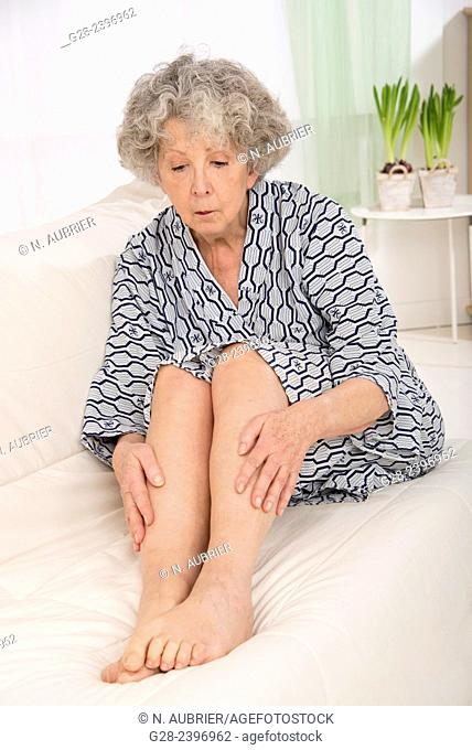Beautiful senior woman holding her suffering legs, sitting on a sofa at home with plants in the background