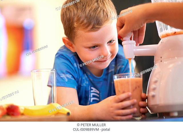 Mother pouring fruit smoothie for son in kitchen