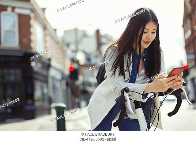 Young woman commuting on bicycle, texting with cell phone on sunny urban street