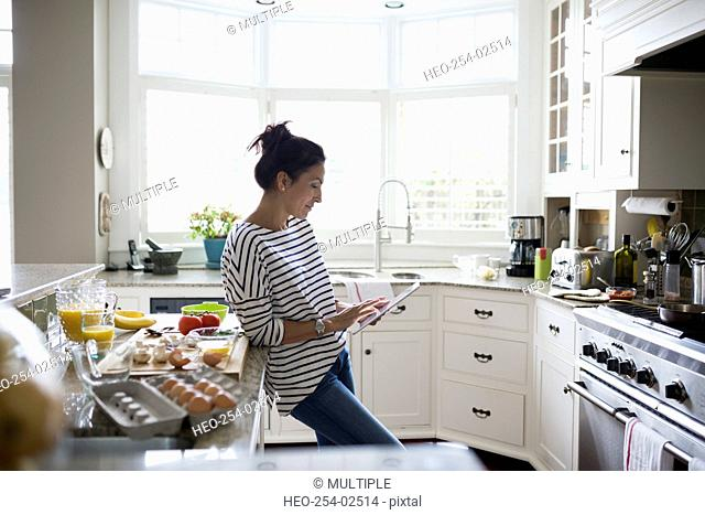 Woman using digital tablet for recipe in kitchen