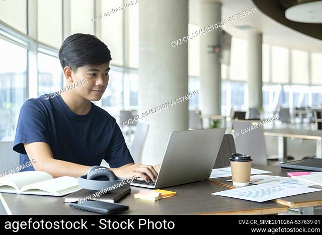 Young collage student using computer and mobile device studying
