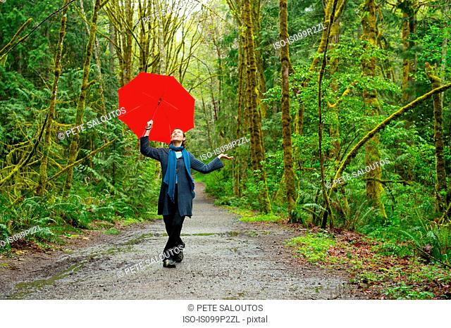 Woman on forest path with red umbrella