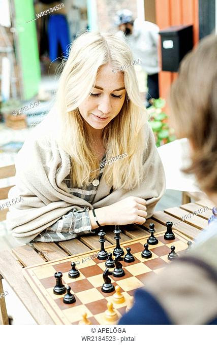Couple playing chess at backyard of cafeteria