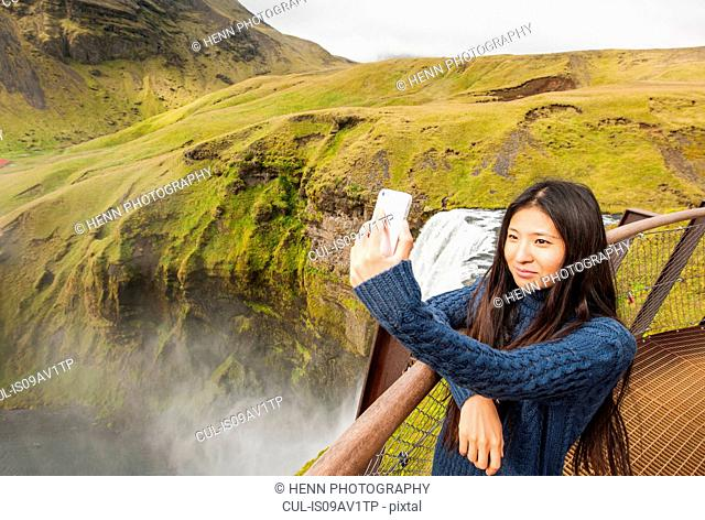 Female tourist taking smartphone selfie at Skogafoss waterfall, Iceland