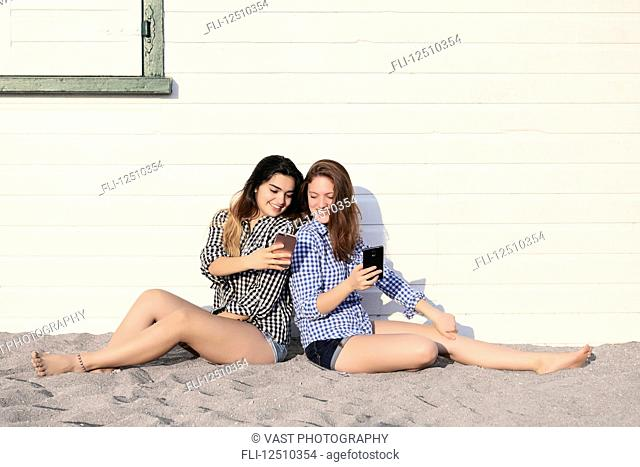 Two teenage girls sitting in the sand against a building looking at their smart phones together, Woodbine Beach; Toronto, Ontario, Canada